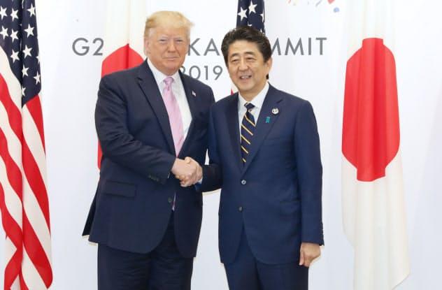 トランプ米大統領と握手を交わす安倍首相(6月、大阪市)=代表撮影