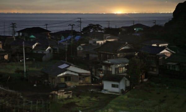 いまだに明かりが戻らない千葉県富津市とは対照的に、対岸の東京湾岸は明かりがともっていた(16日夜)=共同