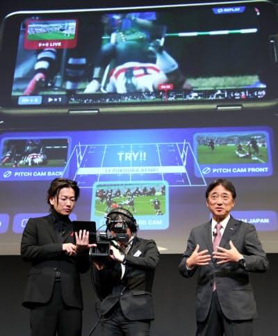 5Gを利用したラグビーの試合観戦サービスを体験する俳優の佐藤健さん(左)とNTTドコモの吉沢和弘社長(18日、東京都中央区)