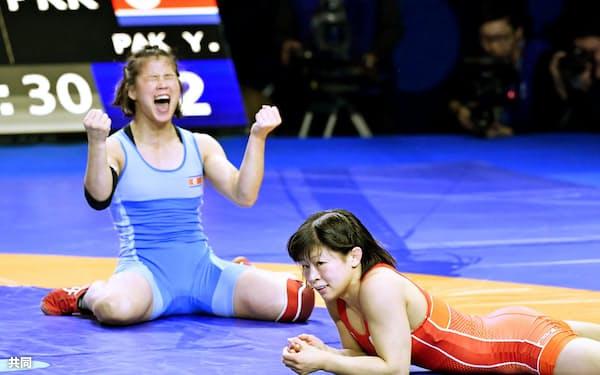 女子53キロ級決勝で北朝鮮のパク・ヨンミ(左)に敗れ、ぼうぜんとする向田真優(18日、ヌルスルタン)=共同