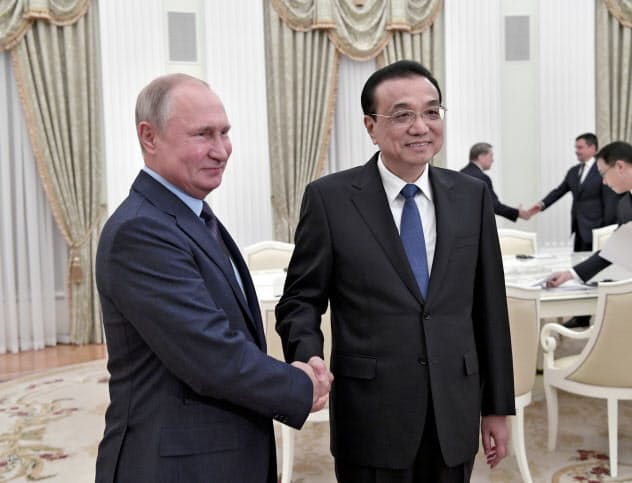 18日、モスクワで会談したロシアのプーチン大統領(左)と中国の李克強首相=ロイター