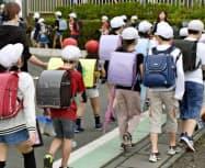 保護者らに付き添われ、集団登校するさいたま市立大谷小学校の児童(19日午前、さいたま市)=共同