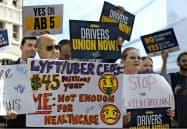 カリフォルニア州で成立した新法により、ウーバーやリフトは運転手を「従業員」として扱わなければならなくなる見込みだ(写真は新法成立を求めていた活動家ら)=AP