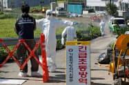 感染拡大の阻止へ養豚場近くの消毒が行われている(18日、韓国・坡州)=聯合・ロイター