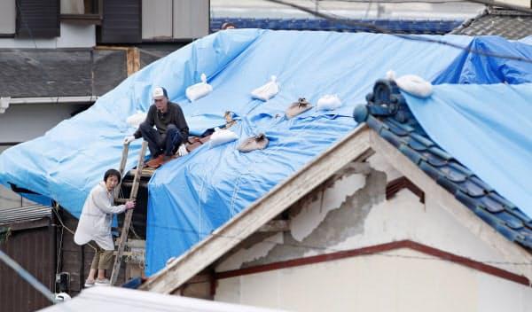 台風15号で被害を受けた住宅で、シートで屋根を覆う作業をする住民(15日、千葉県館山市布良地区)