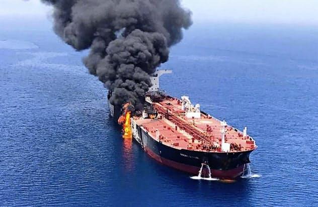6月、ホルムズ海峡付近で攻撃を受けて火災を起こし、オマーン湾で煙を上げるタンカー=AP
