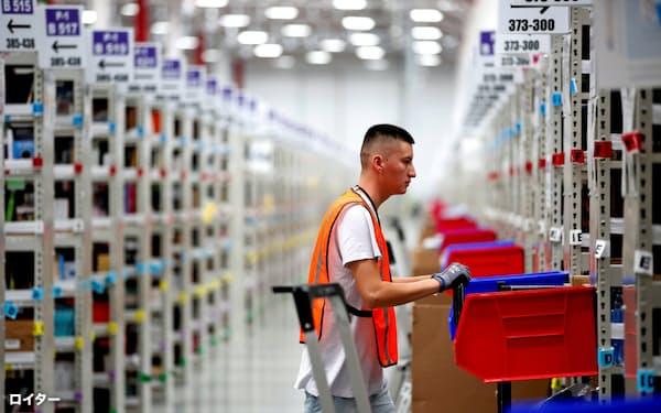 アマゾンの倉庫で働く従業員。同社は巨大プラットフォーマーとして利益をほぼ総取りする「レンティア資本主義の典型」とされる=ロイター