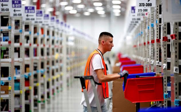 アマゾンの倉庫で働く従業員。同社は巨大プラットフォーマーとして利益をほぼ総取りする「レント資本主義の典型」とされる=ロイター