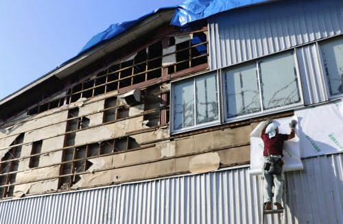 台風15号で被害を受けた壁面の修復作業をする人(19日午後、千葉県八街市)=共同