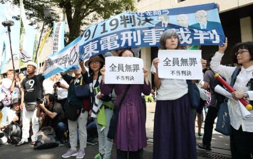 判決を受け、東京地裁前で「全員無罪」の紙を掲げる人たち(19日)