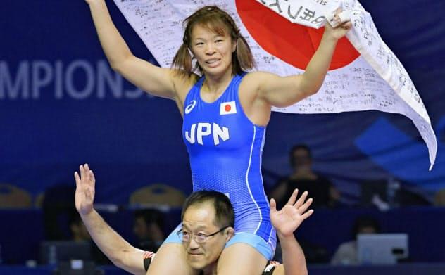 女子57キロ級で優勝し、肩車で日の丸を掲げる川井梨紗子=共同