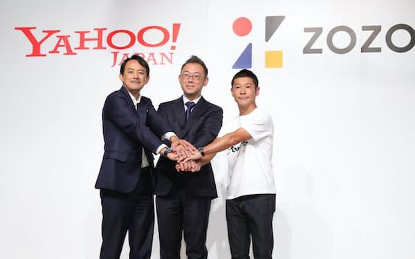 記者会見で握手する(左から)ヤフーの川辺社長、ZOZOの沢田社長、ZOZO創業者の前沢氏(12日、東京都目黒区)