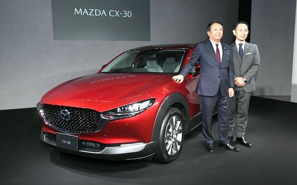 新型SUV「CX-30」を発表するマツダの丸本社長(左)ら(20日、東京都渋谷区)