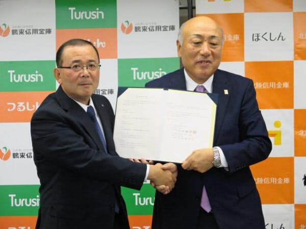 握手する北陸信金の石田理事長(右)と鶴来信金の玉井理事長(20日、金沢市)