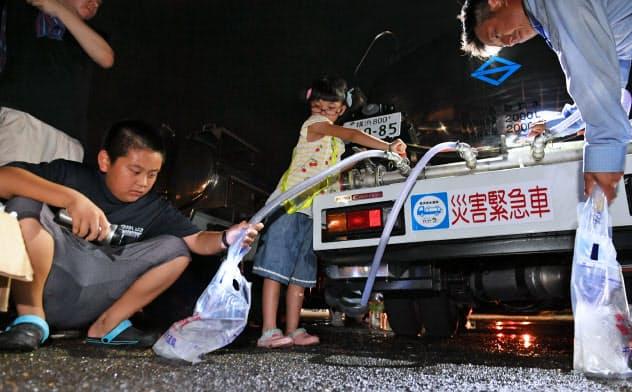 公民館に設けられた給水所で水をくむ地元の人たち(11日、千葉県君津市)