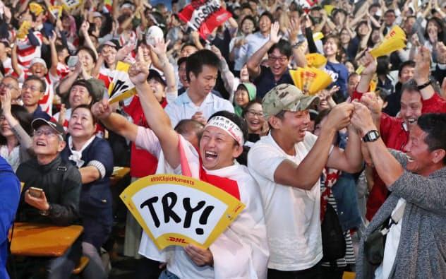 松島選手のトライに喜ぶファン(20日、福岡市博多区のJR博多駅前)