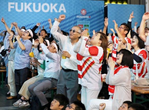日本代表のラブスカフニ選手がトライを決め喜ぶファン(20日、福岡市博多区のJR博多駅前)