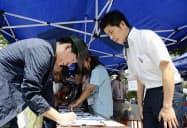 池袋で車が暴走した事故の現場付近で、署名活動する遺族の男性(右)(8月上旬、東京都豊島区)=共同