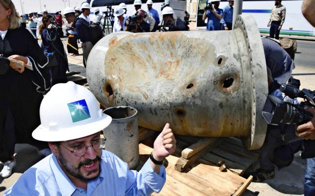 20日、サウジアラビア東部クライス油田への攻撃で、損傷を受けた石油プラントの一部を指さす国営石油会社の関係者=共同