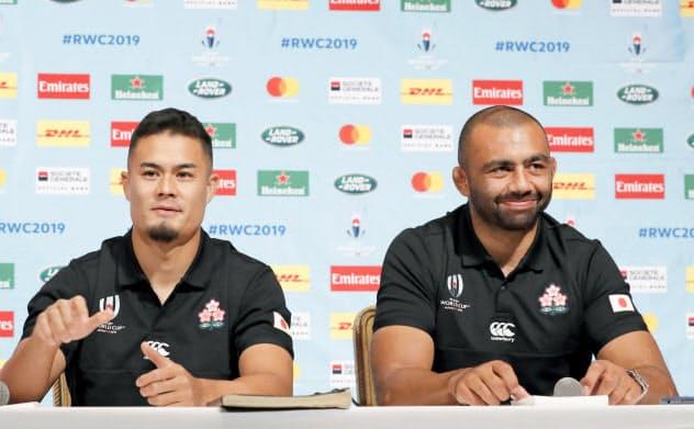ロシア戦から一夜明け、記者会見で笑顔を見せるラグビー日本代表のリーチ主将(右)と田村(21日、東京都内)=共同