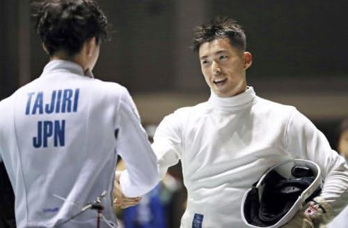 男子エペ3回戦で田尻航大(左)を退け、握手を交わす見延和靖(21日、駒沢体育館)=共同
