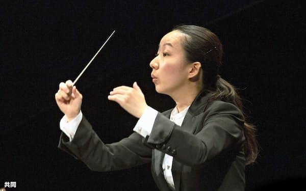 ブザンソン国際若手指揮者コンクールの決勝で指揮する沖澤のどかさん=21日、フランス・ブザンソン(コンクール事務局提供、YVES・PETIT撮影・共同)