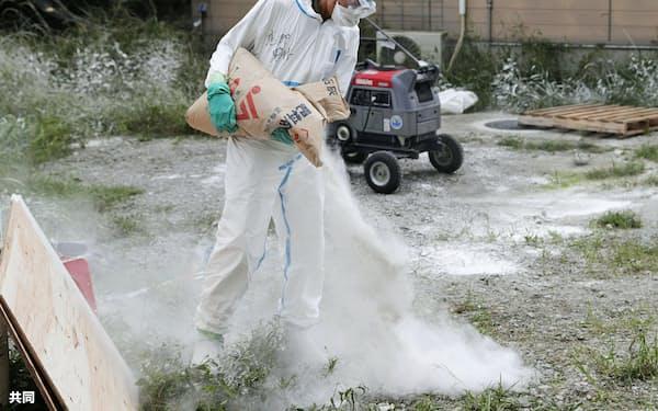 豚コレラが発生した岐阜県恵那市の養豚場で、石灰をまく作業員(22日午後)=共同