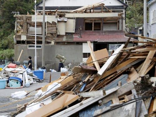 台風15号の影響で屋根や壁が壊れた家屋と積み上げられたがれき(22日午後、千葉県鋸南町)=共同