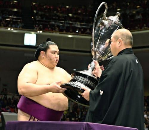 大相撲秋場所で2度目の優勝を果たし、日本相撲協会の八角理事長から賜杯を受け取る関脇御嶽海=共同
