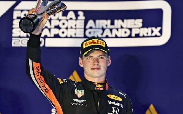 F1シンガポールGPで3位に入り、表彰台でトロフィーを掲げるレッドブル・ホンダのマックス・フェルスタッペン(シンガポール)=ゲッティ共同