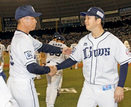 19日の日本ハム戦で5勝目を挙げ、辻監督(左)と握手を交わす十亀。監督もびっくりの2試合連続無失点勝利だった=共同