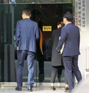 家宅捜索のため、韓国の曺国法相の自宅があるマンションに入る検察関係者(23日、ソウル)=聯合・共同