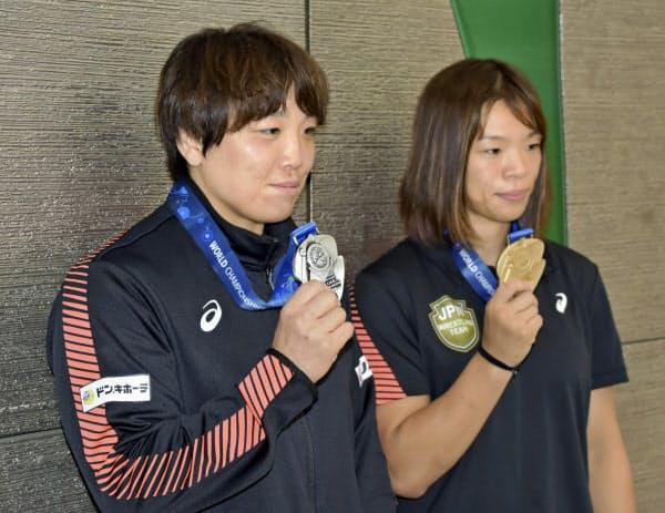 レスリングの世界選手権から帰国し、獲得したメダルを手にする川井梨紗子(右)と皆川博恵(23日、成田空港)=共同