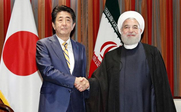イランのロウハニ大統領(右)と握手する安倍首相(24日、米ニューヨーク)=共同