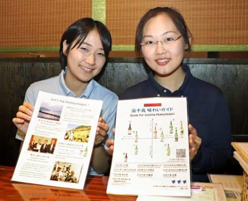 日本酒を紹介するカードを手にする羽賀杏菜さん(左)と中村千尋さん(岩手県釜石市)=共同