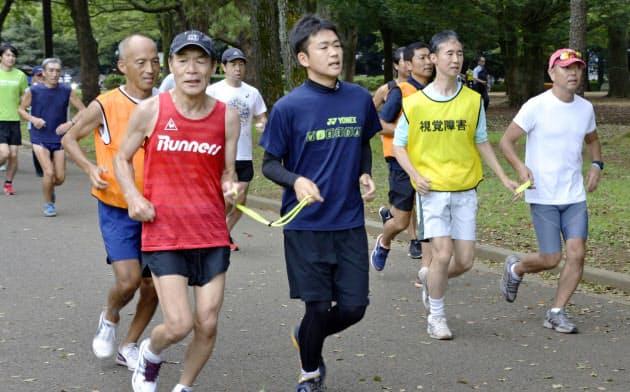 日本ブラインドマラソン協会が開いた伴走者の練習会で、ランニングする参加者ら(1日、東京・代々木公園)