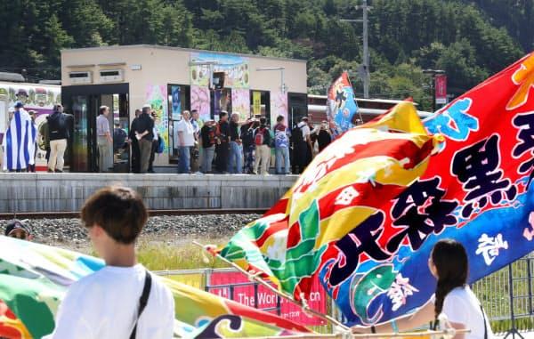 大漁旗に出迎えられる観戦客ら(25日、岩手県釜石市)