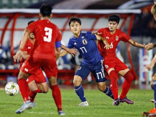 久保建(中央)を囲むミャンマーの選手たち。ミャンマーは敗れはしたが善戦だった=共同