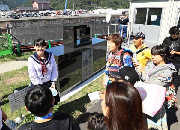 会場を訪れたファンに震災の教訓を語る地元の高校生(25日、岩手県釜石市)