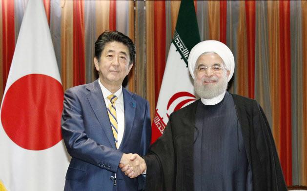 会談を前に握手するイランのロウハニ大統領(右)と安倍首相(24日、米ニューヨーク)=共同