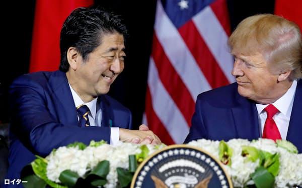 安倍首相(左)とトランプ米大統領は日米貿易協定の最終合意を確認した(ニューヨーク)=ロイター