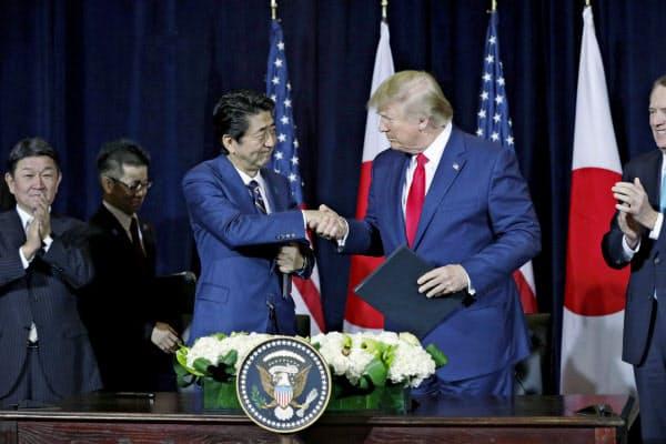 日米貿易協定締結で最終合意し、合意文書への署名を終えて握手する安倍首相(左)とトランプ大統領=9月25日、米ニューヨーク(共同)