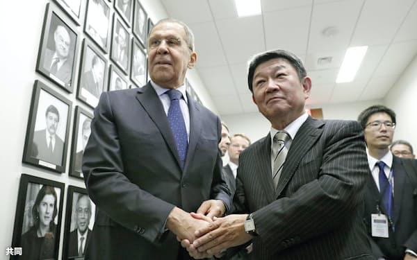 会談を前に、ロシアのラブロフ外相(左)と握手する茂木外相(25日、米ニューヨーク)=共同