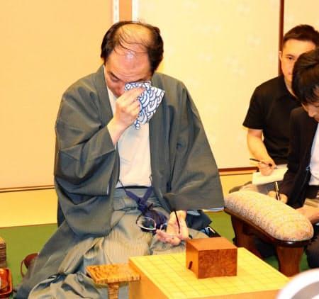終局後のインタビューで涙を拭う木村新王位(26日、東京・千代田の都市センターホテル)
