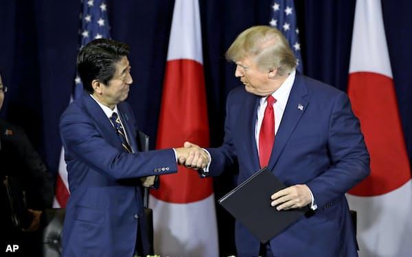 日米貿易協定締結で最終合意し、共同声明に署名を終え握手する安倍首相とトランプ米大統領(25日、ニューヨーク)=AP