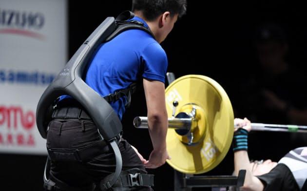 大会でパワーアシストスーツを着用し補助するボランティア(26日、東京都千代田区)