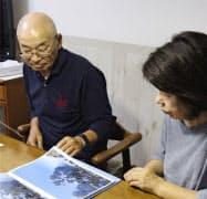 御嶽山の噴火で犠牲になった近江屋洋さんが撮影した写真を見る父、勇蔵さんと母、初子さん(21日、横浜市)=共同