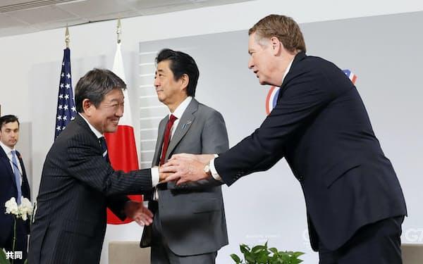 ライトハイザー氏(右)と握手する茂木氏。中央は安倍首相(8月25日、フランス南西部ビアリッツ)=共同