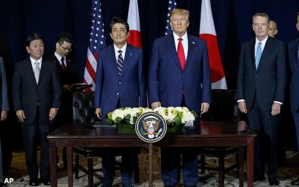 合意文書の署名式。日米首脳を挟んで茂木敏充外相(左端)とライトハイザー米USTR代表(右端)(25日、ニューヨーク)=AP