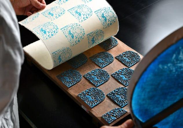 江戸時代に彫られた板木に顔料をのせ、「花兎」の文様を和紙に写し取る=小幡真帆撮影